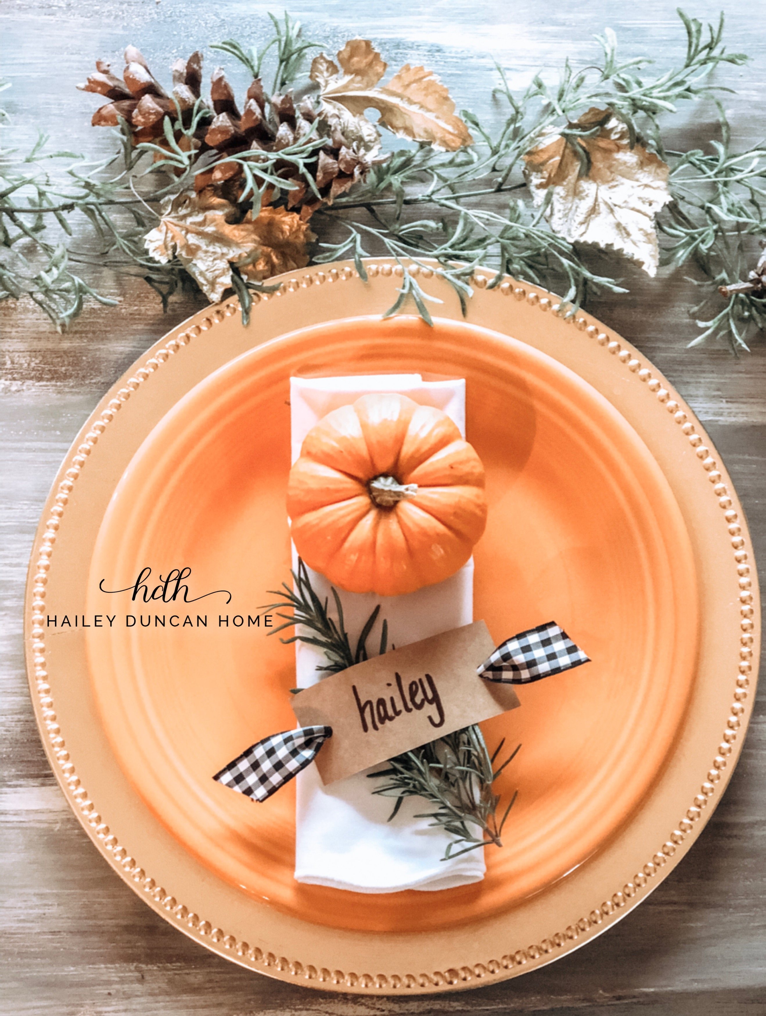 Thanksgiving Place Setting with pumpkin and name card on orange plate