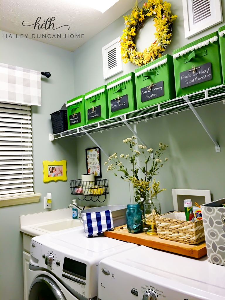 Organized laundry room with green storage bins above washer and dryer. - Hailey Duncan Home