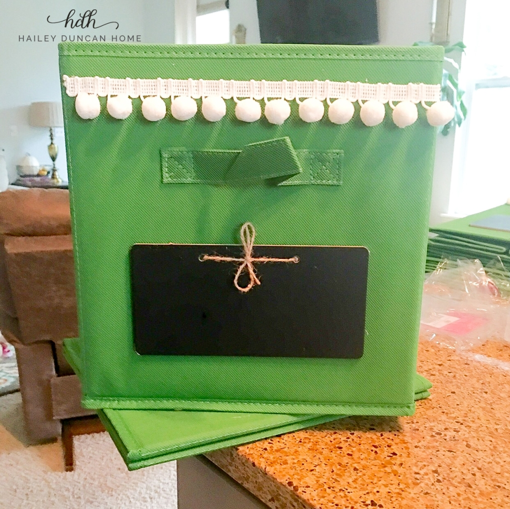 Green storage bin with white pom poms and chalkboard label.