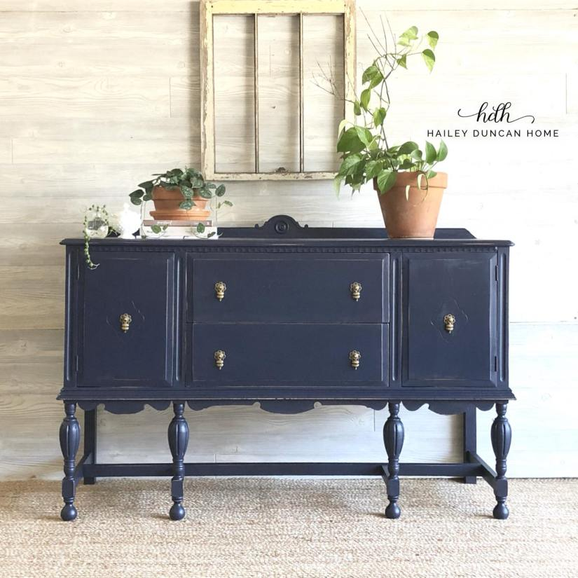 Navy painted buffet by Hailey Duncan Home. Buffet has some books and plants sitting on top.