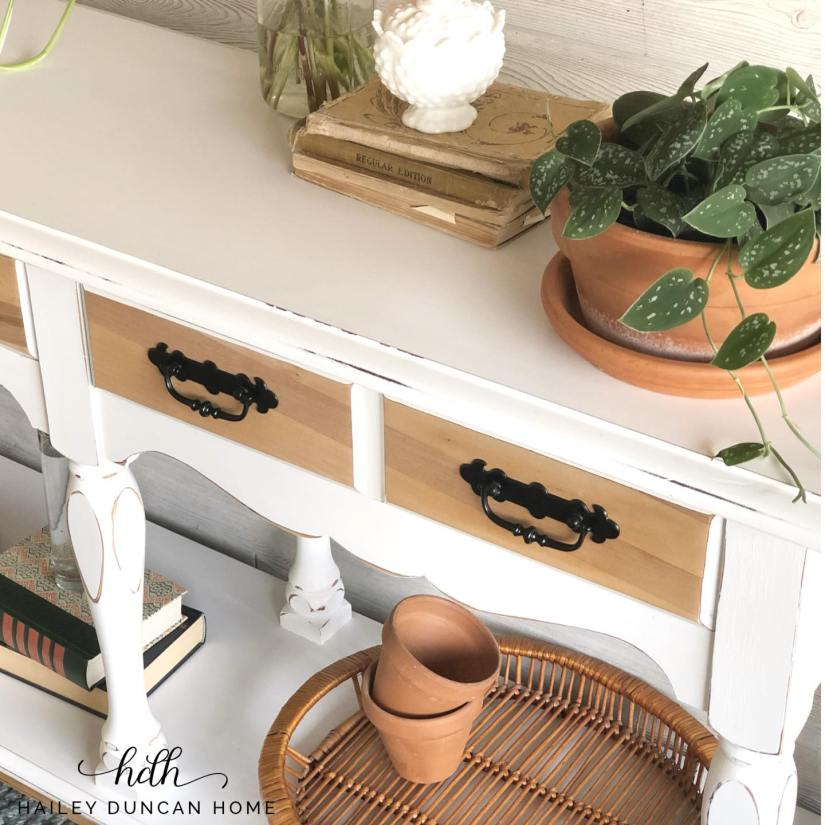 Close up of a painted entry table. Painted white with raw wood drawer fronts. Black painted hardware.